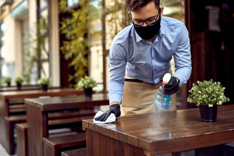 man in mask cleaning restaurant table