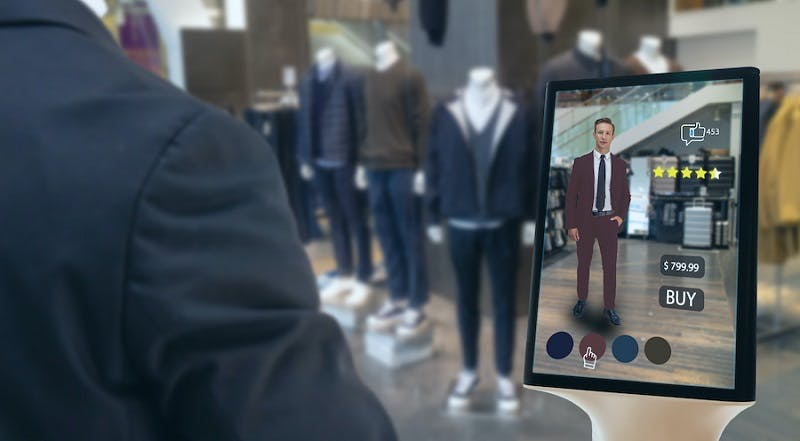 A person standing in front of a virtual try-on screen. Their avatar on the screen wears a suit, with a 4.5 star rating next to it. Underneath is a $799.99 price tag with the word BUY beneath.