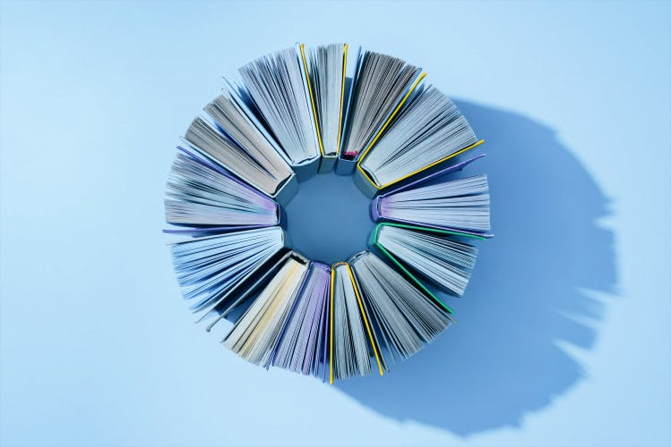 books standing on edge in circle formation on light blue background