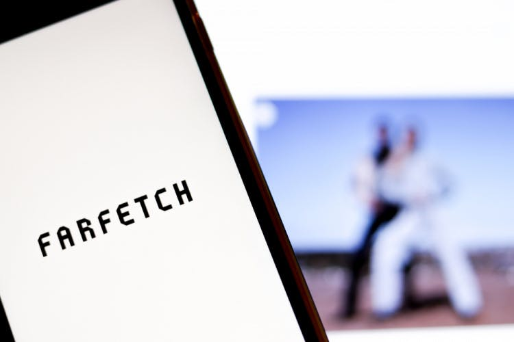 Farfetch logo on smartphone screen in front of the brand website