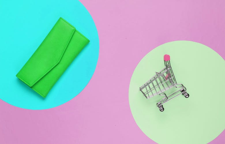 wallet and miniagreen wallet on blue circle and miniature shopping basket on green circle on pink backgroundture shopping basket on pink background