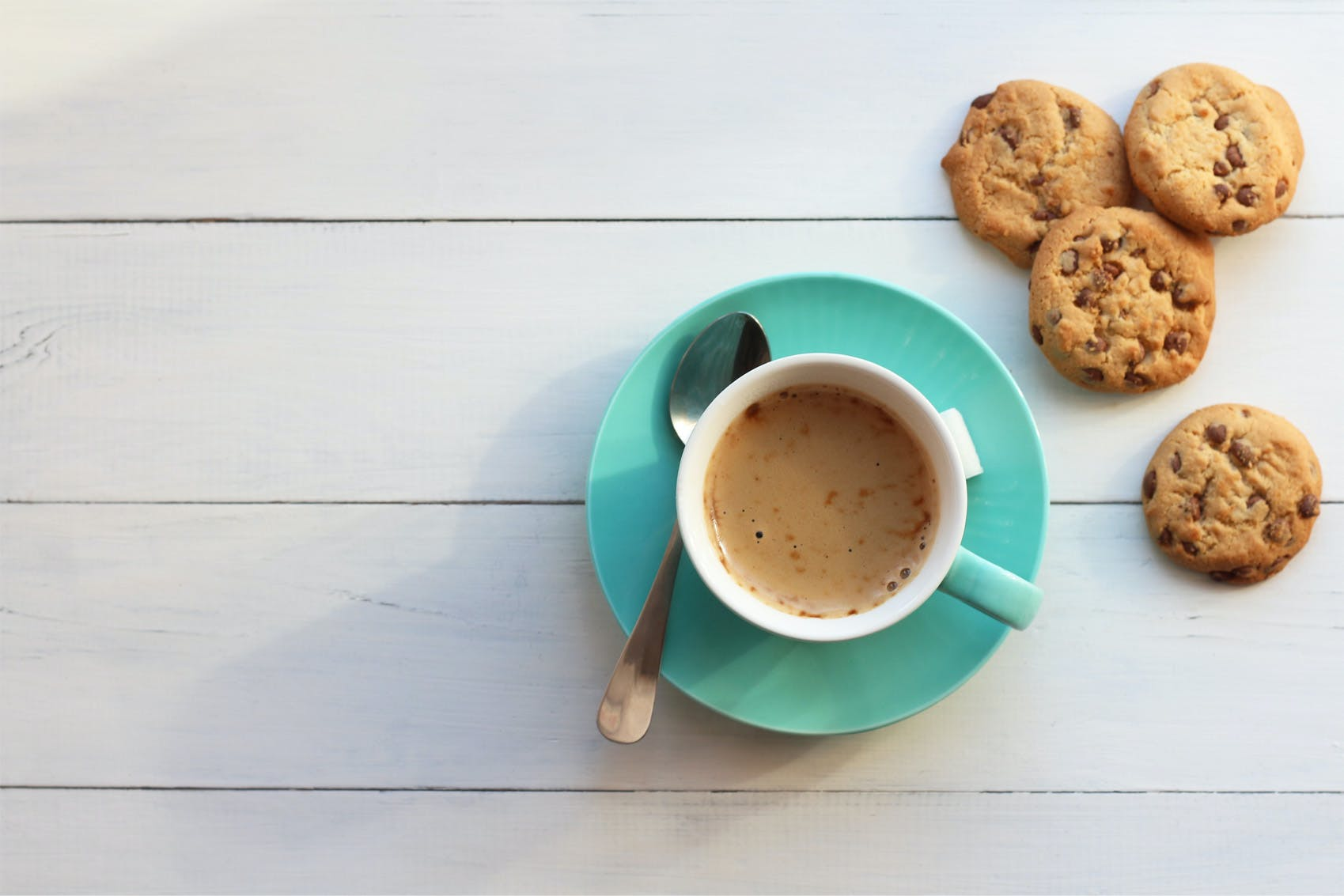 coffee in a turquoise cup on a saucer and cookies on a white background