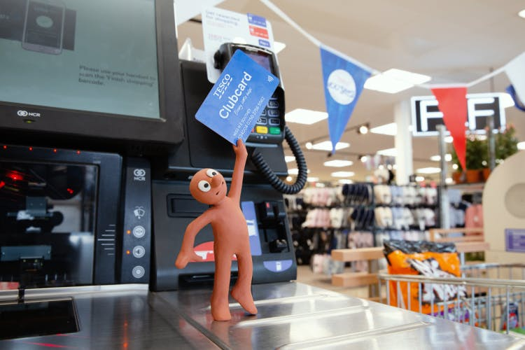 Morph holding a Tesco Clubcard to card reader at self-service checkout in Tesco supermarket in Prices That Take You Back campaign
