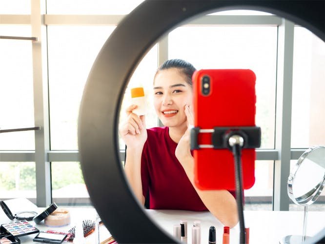 Female beauty influencer demonstrating product on livestream filming on mobile phone with light ring
