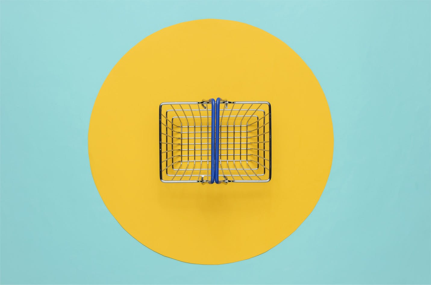 Mini shopping basket on blue background with yellow circle. Top view