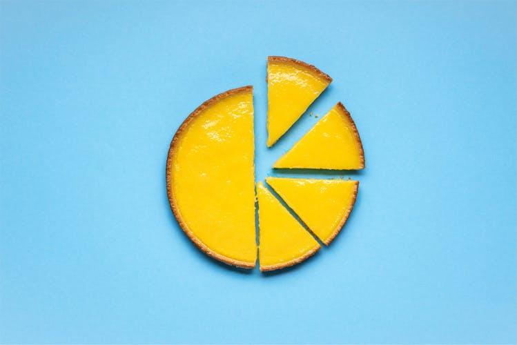 Lemon pie sliced on a blue background