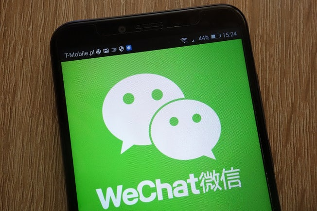 WeChat logo in English with Chinese characters on a smartphone screen.